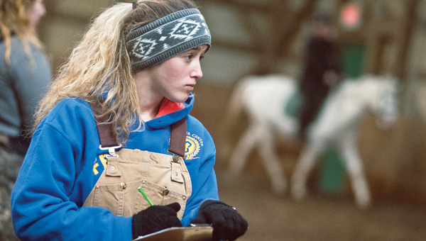 Patty Rife, student at Collins Career Center, watches students from the Ohio University Horse Park put the park's horses through routines during a special equine class for high school students on Saturday.
