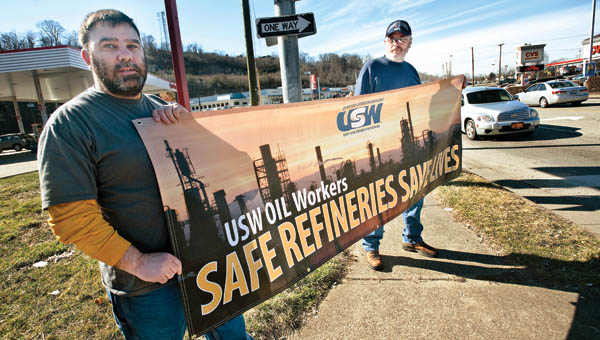 Mike Roark, left, and Curt Maynard, right, hold a sign at the corner of the Speedway gas station along 13 Street in Ashland as they and other Marathon Petroleum employees continue their protest efforts.