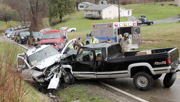 Emergency personnel work to aid a driver in a two-vehicle accident on State Route 243.