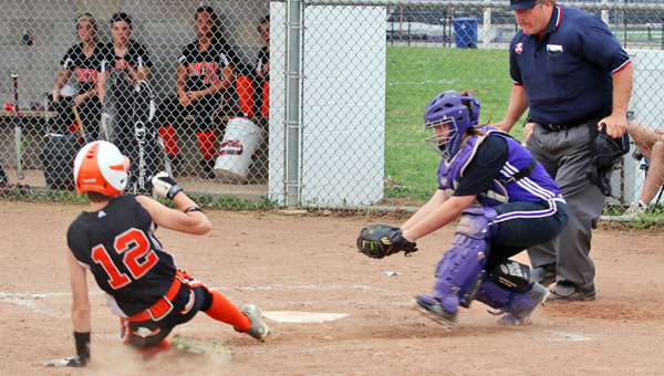Ironton Lady Fighting Tigers' Kylie Barcus (12) slides safely across home plate ahead of the tag by Chesapeake catcher Kelsey Huff during an OVC game on Monday. (Courtesy of Tim Gearhart of Tim's News & Novelties of Ironton)
