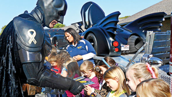Batman, also known as John Buckland, meets with students at Burlington Elementary School on Monday to give out smoke detectors.
