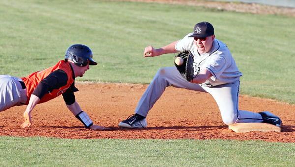 Coal Grove Hornets' first baseman Jeb Jones (right) makes the catch on a pickoff throw attempt as he prepares to tag out a Raceland Rams' baserunner. Coal Grove outlasted the Rams 16-15 on Wednesday. (Courtesy of Tim Gearhart of Tim's News & Novelties of Ironton)