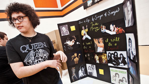 Noah Ratliff talks about his project on Freddie Mercury during the Ironton High School Social Studies Fair Wednesday. Project themes included on Adolph Hitler, David Koresh, Alcatraz Island, moon landing and conspiracies.