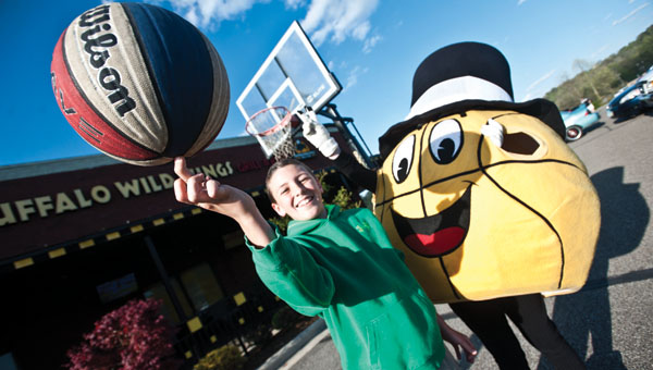 J.C. Damron and the Gus Macker mascot ham it up while shooting free throws during a promotional event Thursday at Buffalo Wild Wings.