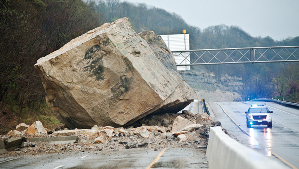 An Ohio State Highway Patrol cruiser looks small compared to the two-story boulder blocking U.S. 52 on Friday morning. The rockslide occurred around 3 a.m.