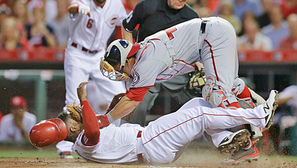 Cincinnati's Marlon Byrd scores ahead of the tag by Washington Nationals' catcher Wilson Ramos during the sixth inning of Friday's game. The Reds won 5-2. (Courtesy of the Cincinnati Reds.com)