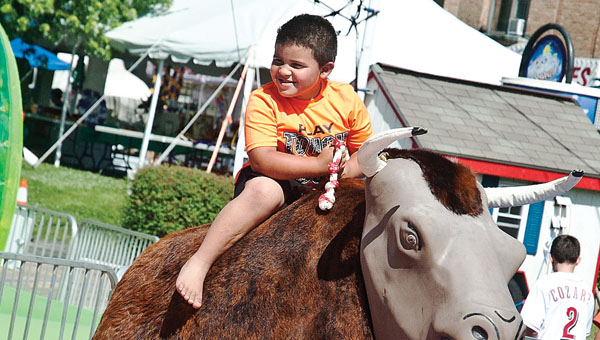 Five-year-old Jacarr Coleman attempts to ride the bull during the annual Charity Fair sponsored by the Ironton Catholic Schools.