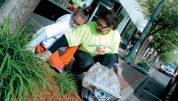 Ayanni Estes, left, and Carol Seward, right, represent the Ohio Association of Youth Clubs as they volunteer Saturday morning in downtown Ironton during the Great American Clean Up.