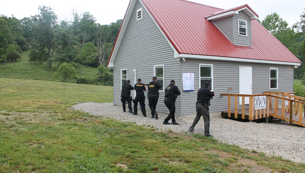 Members of the Lawrence County SWAT team get ready to arrest a gunman during a simulation Thursday at the dedication of the public safety training facility at Collins Career Center.