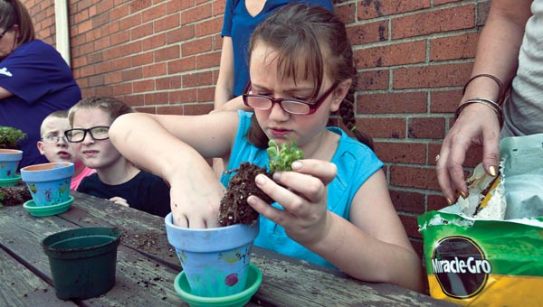 Lyndis Wilburn plants flowers on Friday as part of a Mother's Day project with other students from Open Door School. Raven Webb plants flowers with her fellow students.