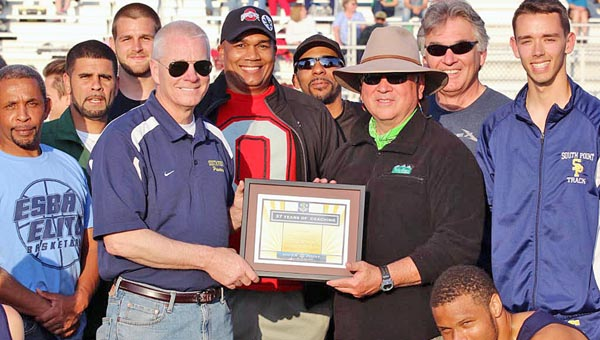 South Point High School's annual invitational track meet took time to honor former Pointers' head track coach Randy Smith with a plaque for his 37 years of service. Smith is surrounded by many of his former players as he accepts the plaque presented to him by South Point superintendent Mark Christian. (Courtesy of Tim Gearhart of Tim's News & Novelties of Ironton)