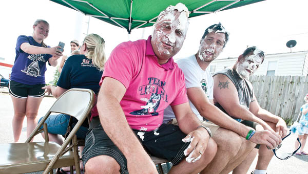 Freddie Hayes, Adam Alt and David Davenport, left to right, take one pie in the face after another.