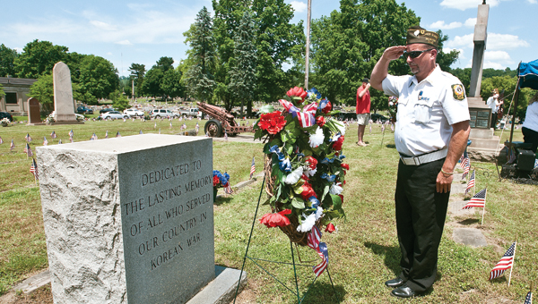 Dave Johnson with the VFW Post 8850 Honor Guard performs the placement of the memorial wreaths during the Veterans Memorial Service on Sunday.