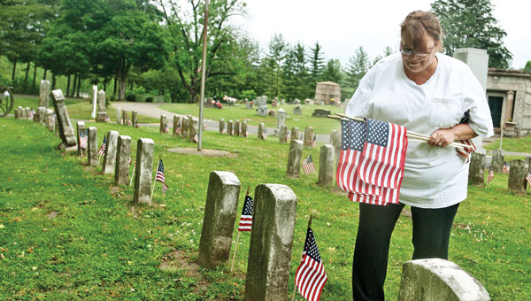 Julia Jones decorates soldiers' graves at Woodland Cemetery early Saturday morning in honor of Memorial Day.