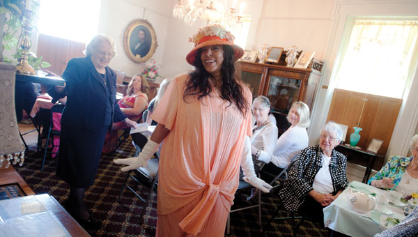 Jackie DuFore shows off a dress that a woman living in the 1920s would have worn on Saturday during the Garden Party Tea event at the Lawrence County Museum.