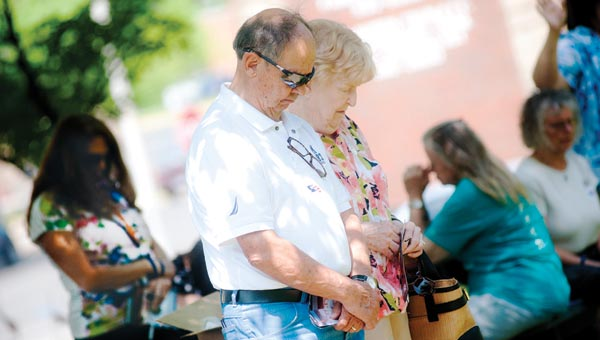 Ralph and Margy Kelley bow their heads in prayer Thursday afternoon, in front of the Lawrence County Courthouse.