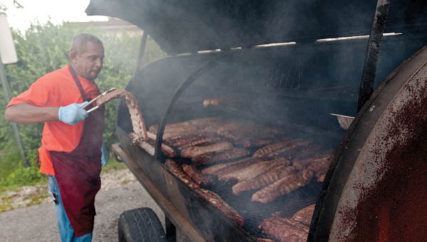 Aaron Jackson is the man of the hour as he barbecues ribs for the Burlington Courthouse Project kickoff Saturday at the Commons Park.