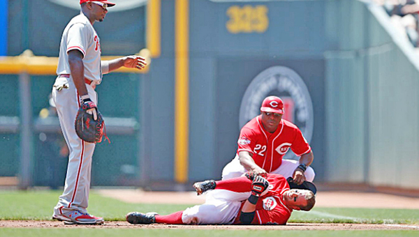 Cincinnati Reds' shortstop Zack Cozart grabs his knee in pain after being injured during the first inning while running out a ground ball. Cozart is expected to go on the disabled list. The Reds beat the Philadelphia Phillies 5-2 to complete a three-game sweep. (Photo Courtesy of The Cincinnati Reds)