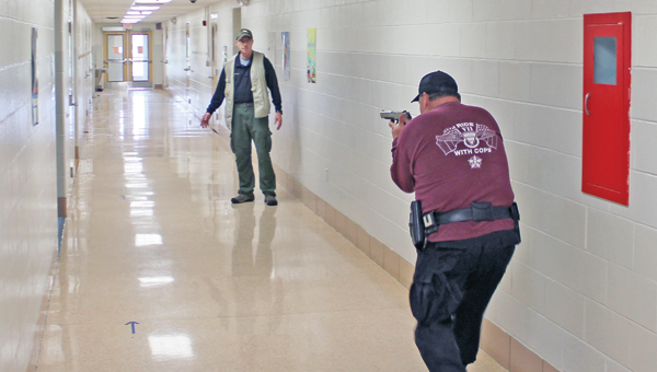 Sgt. Steve Cartmell of the Lawrence County Sheriff's Office gets practice in hunting down a school shooter in front of Tactical Defense Institute (TDI) instructor Chris Wallace at Rock Hill Schools Thursday morning during a TDI training session with Rock Hill teachers and local law enforcement officers.