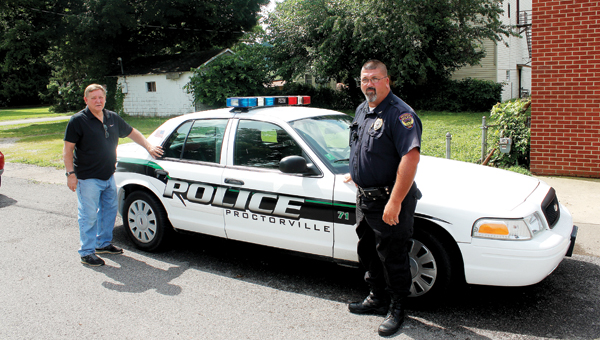 Proctorville Mayor Rick Dunfee and Proctorville Police Chief Bill Murphy next to the police department's newest cruiser.