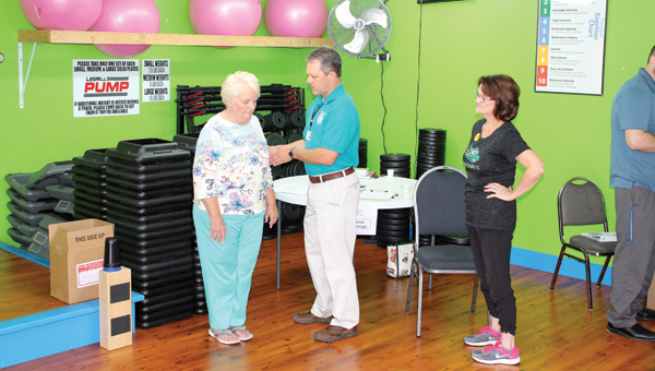 Phil Simpson from Cabell  Huntington Hospital gives balance screenings at the senior health fair at Brickhouse Cardio Club in Proctorville on Friday.