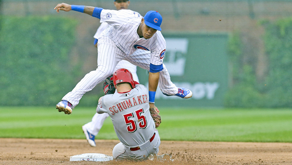 Chicago Cubs second baseman Addison Russell tags out the Cincinnati Reds' Skip Schumaker (55) trying to steal second base during the second inning at Wrigley Field in Chicago on Friday. The Reds won 5-4 in 10 innings. (MCT Direct Photo)