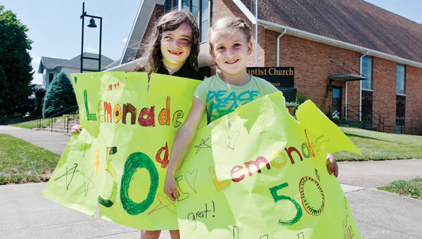 Seven-year-old Lori Belle Boyd, left, and Lexi Barnes, 6, sell glasses of homemade lemonade, on the corner of Fifth Street for a youth mission project at First Baptist Church in Ironton Friday.