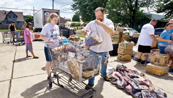 Brooke Ferguson, left, and Greg Jackson, right, help out during a food giveaway at the First Nazarene Church on Tuesday in Ironton.
