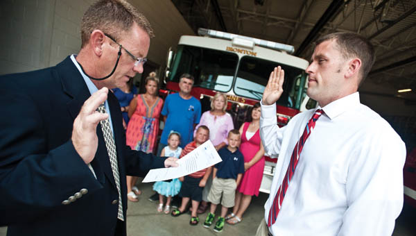 Ironton Mayor Rich Blankenship swears in Joe Laber as Ironton's newest firefighter Friday while his family watches.