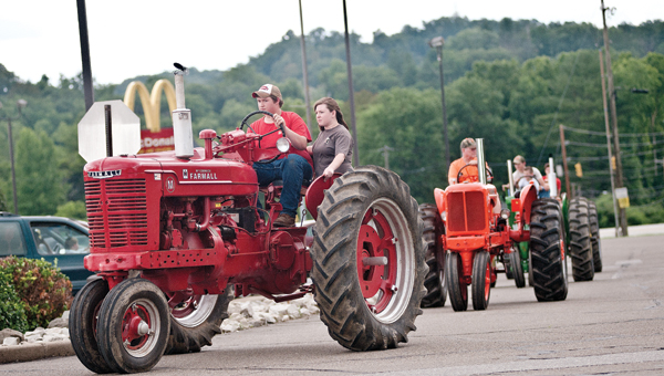 Participants of Ironmasters Days take their tractors for a ride through the parking lot of the Ironton Hills Shopping Plaza for a parade on Saturday.