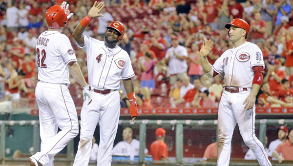 Jay Bruce (left) is congratulated by Brandon Phillips (4) and Joey Votto after hitting a three-run homer in the eighth inning on Saturday. Bruce drove in all four runs as the Reds lost 9-4 to the Cleveland Indians. (Courtesy of the Cincinnati Reds.com)