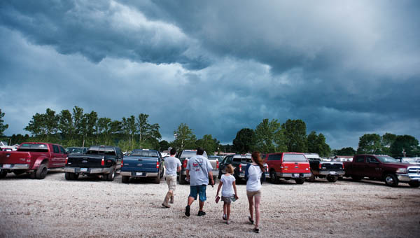 A family makes their way to their vehicle as storm clouds quickly roll in over the fairgrounds Monday.