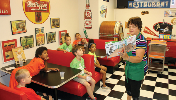 Junior Master Chef instructor Gloria Dewitt reads a story after students made and ate pizza.