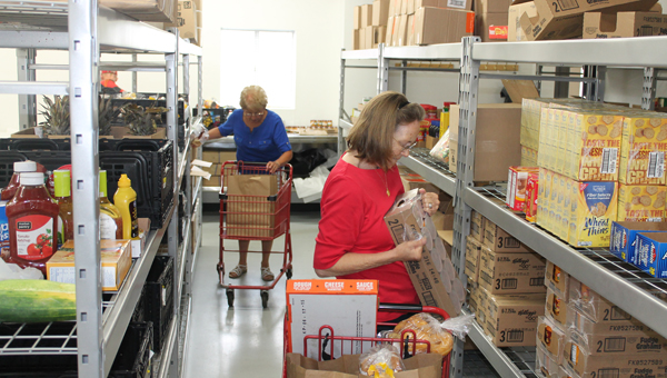 Ironton First United Methodist Church Harvest for the Hungry volunteers Bobbi Shelton (back) and Lil Hart gathering food for people Monday morning at the food pantry during a normal distribution.