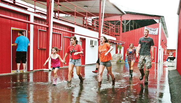 People make their way through extra large water puddles following a second storm to hit the Lawrence County Fairgrounds.