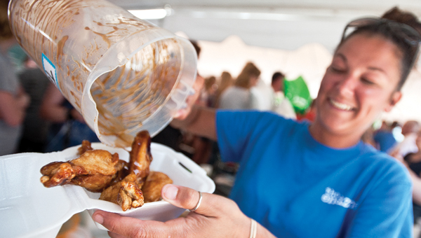 Tara Pierce, with the End Zone, serves up chicken wings during Taste of Ironton on Saturday.
