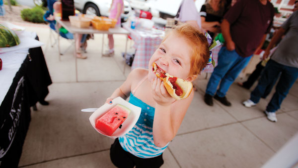 Six-year-old Joshline Sanford bites into her hot dog while at the Ironton Farmers Market on Saturday. This week Ironton in Bloom hosted a cookout with hot dogs and watermelon.