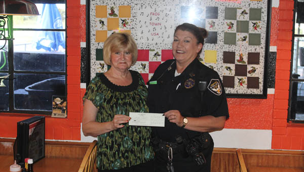 Frogtown owner Darlene Rutledge give a donation check to Captain Pam Wagner of the Ironton Police Department for the Fraternal Order of Police.