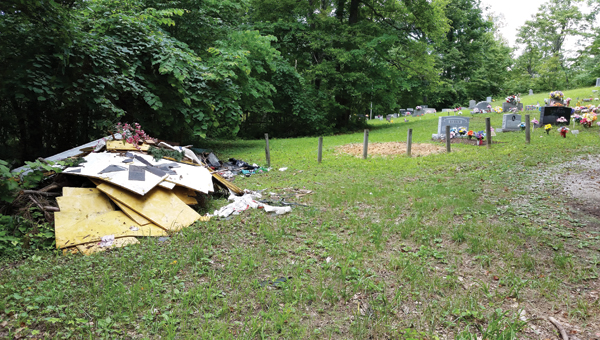 Piles of trash were dumped at Ross Cemetery in Kitts Hill in June. The person responsible was cited to court by the Lawrence-Scioto Solid Waste Management District.