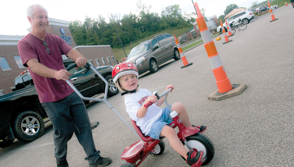Two-year-old Paeson Mineer rides through the obstacle course with John Dickess in tow during National Health Center Week bike.