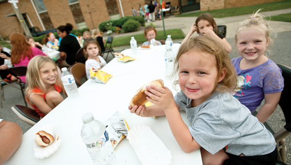 Kenadee Sharp, far right, enjoys a hotdog with her friends while taking part in the street fair Friday evening at the First Baptist Church in Ironton.