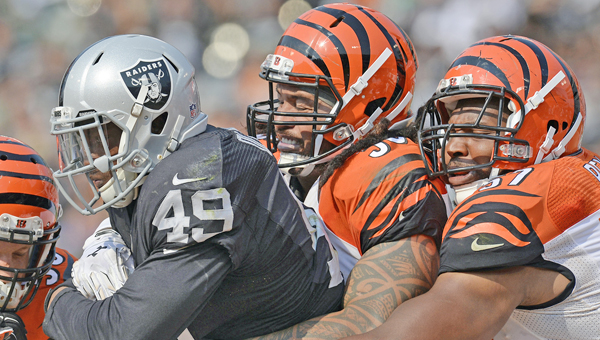 The Oakland Raiders' Jamize Olawale (49) is tackled by the Cincinnati Bengals' Rey Maualuga (58) and Vincent Rey (57) in the third quarter at O.co Coliseum in Oakland, Calif., on Sunday The Bengals won 33-13. (MCT Direct Photos)