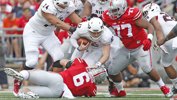 Ohio State defensive linemen Sam Hubbard (6) and Michael Hill (77) take down Northern Illinois quarterback Drew Hare (12) on a third down in the second quarter at Ohio Stadium in Columbus on Saturday. (MCT Direct Photo)