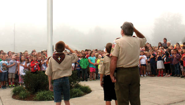 Dawson-Bryant Elementary students and Boy Scouts Landon Davis and Tyler Nutter salute the flag after lowering it at the school's Patriot Day ceremony Friday morning.