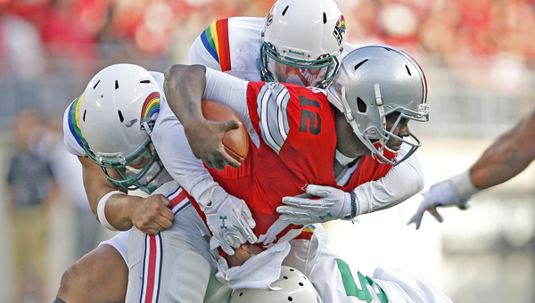 Ohio State quarterback Cardale Jones (12) is taken down for a sack by Hawaii linebacker Makani Kema-Kaleiwahea (55) and teammates in the third quarter at Ohio Stadium in Columbus on Saturday. Ohio State won, 38-0. (MCT Direct Photo)