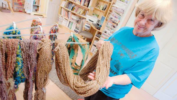 Judy Ross displays spun yarn along with homemade scarves and novelties.
