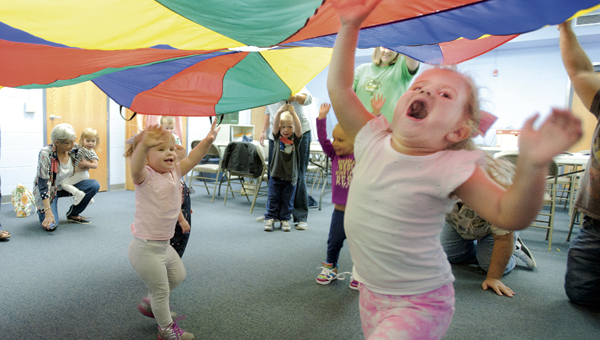 Sisters Lily, left, and Olivia Dalton, right, enjoys the parachute game during Toddler Time at the Briggs Lawrence County Public Library Ironton Branch Tuesday.