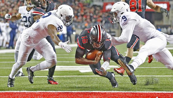 Ohio State quarterback J.T. Barrett (16) slides between Penn State safeties Jordan Lucas (9) and Marcus Allen (2) for a second-quarter touchdown at Ohio Stadium in Columbus, Ohio, on Saturday, Oct. 17, 2015. (Chris Russell/Columbus Dispatch/TNS)