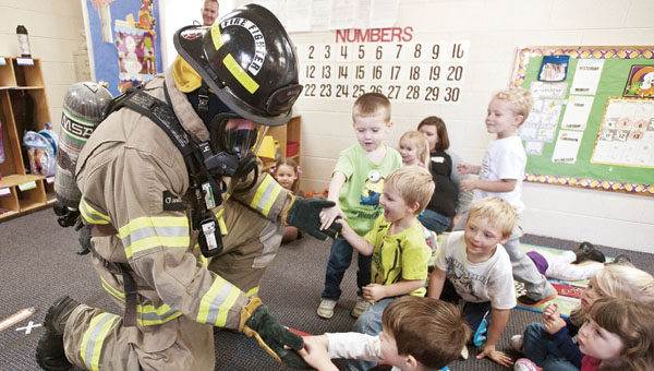 Zack Kriebel, with the Ironton Fire Department, visits with children at the Central Christian Daycare during a special fire safety visit Tuesday.