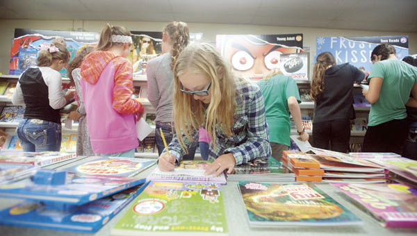 Kaitlyn Fleming makes a list of books she would like to buy during the annual book fair at Fairland Middle School.